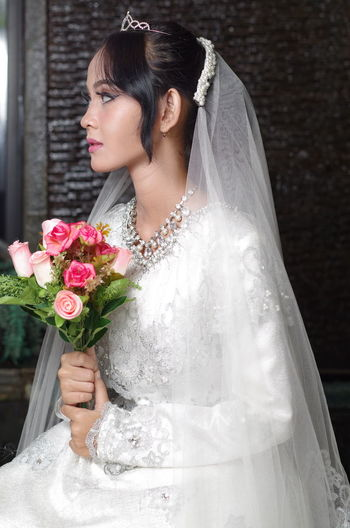 Bride holding bouquet sitting against wall