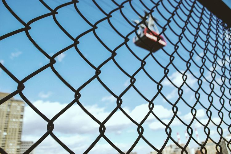 Overhead cable car viewed through chainlink fence