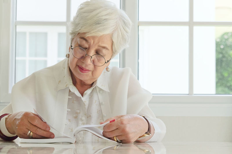 Senior woman reading book while sitting at home
