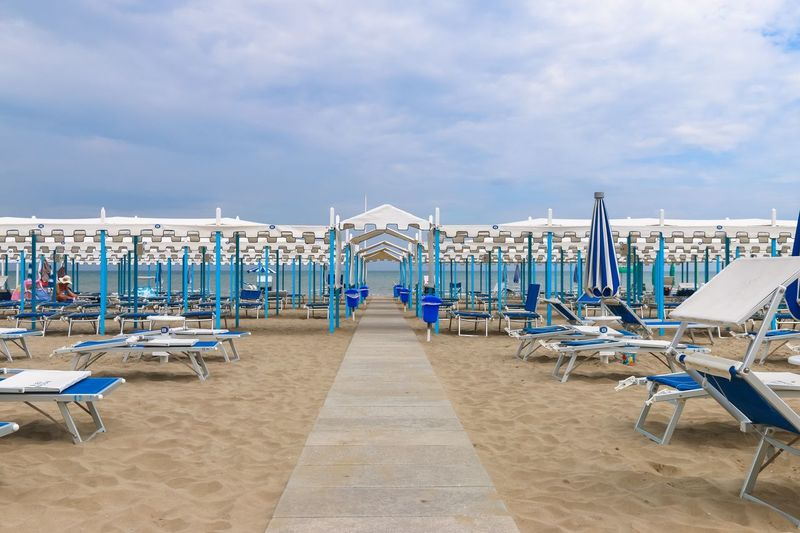 Empty beach, Italy, Riccione Italy. Riccione Italy Emiliaromagna Rimini Riccione Resort No People Chaise Lounge Sunbed Beach Pathway In A Row Sky Beach Cloud - Sky Arrangement Sea Order Sand Sun Lounger Outdoors Large Group Of Objects Tranquility Day Chair Canopy Blue Vacations