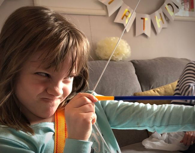 Close-up of girl aiming archery at home