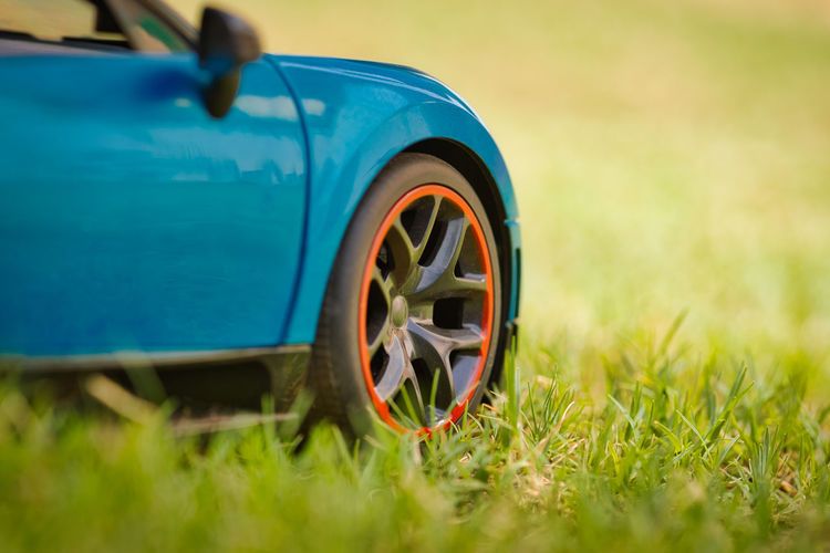 Close up car tyre Blue Car Day Field Grass Green Color Land Land Vehicle Macro Mode Of Transportation Motor Vehicle Nature No People Outdoors Plant Profile View Retro Styled Selective Focus Sports Car Tire Toy Toyphotography Transportation Wheel