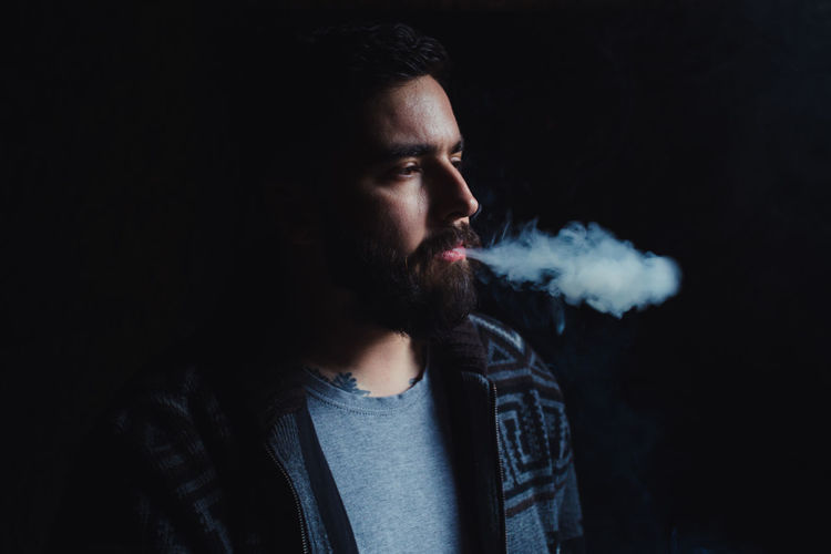 Beard Style Smoking Smoke Heritage Lumber Industry Smoke - Physical Structure Smoking Issues Smoking - Activity Bad Habit Cigarette  Activity Social Issues One Person Young Adult Portrait Men Adult Warning Sign Tobacco Product Young Men Headshot Sign Black Background Dark