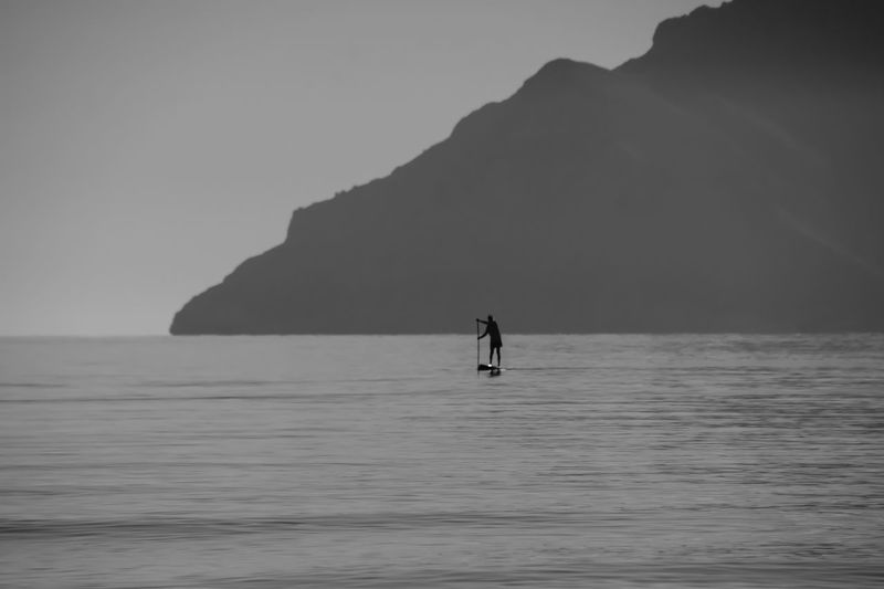 Silhouette man paddleboarding on sea against mountain during foggy weather