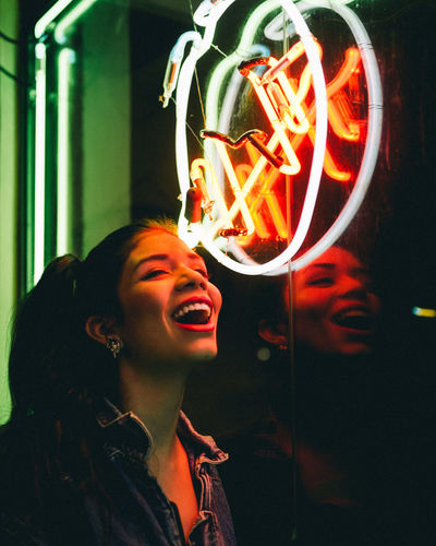 Young Woman Laughing Against Neon Sign On Window During Night