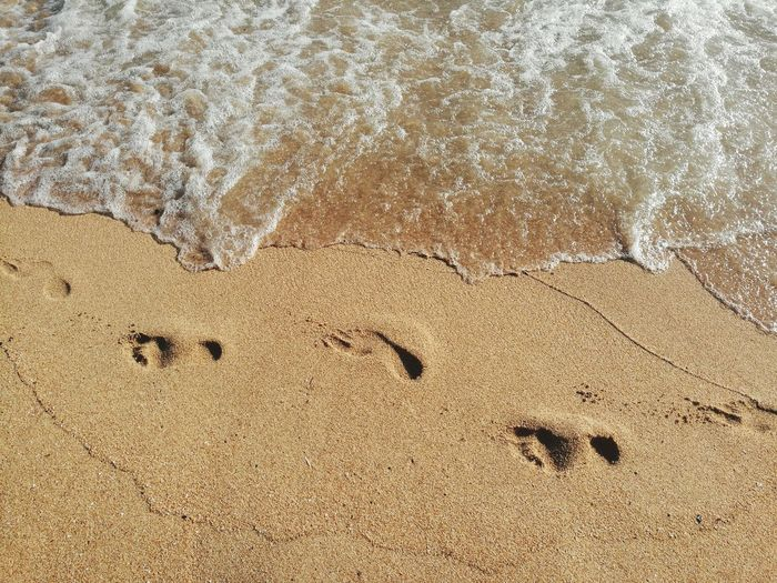 High angle view of footprints on shore at beach
