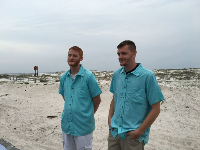 Friends standing on beach against sky