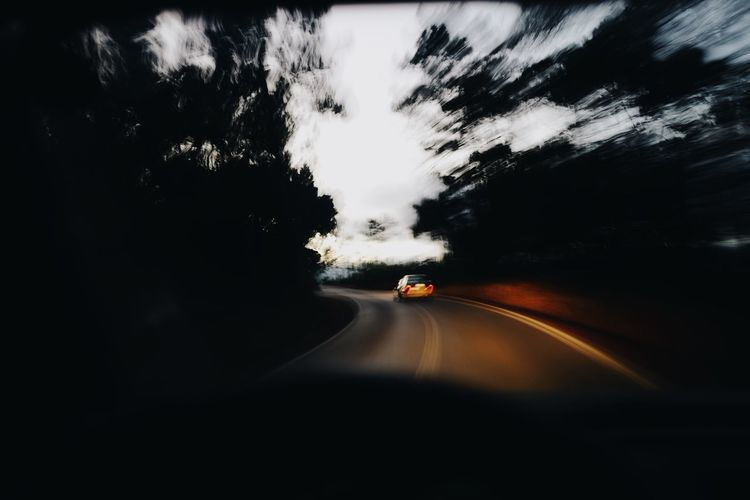 Road amidst silhouette trees against sky seen through car windshield