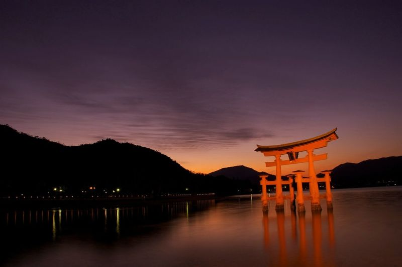 Itsukushima Shrine At Lake Against Sky During Sunset