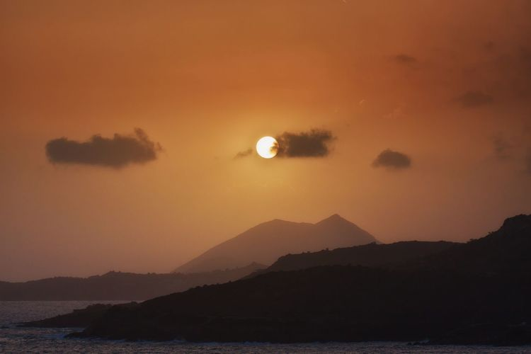 Scenic sea view from the Temple of Poseidon. Scenics - Nature Beauty In Nature Sky Sunset Mountain Tranquil Scene Tranquility Water Silhouette Orange Color No People Idyllic Sun Nature Cloud - Sky Mountain Range Sea Outdoors Non-urban Scene