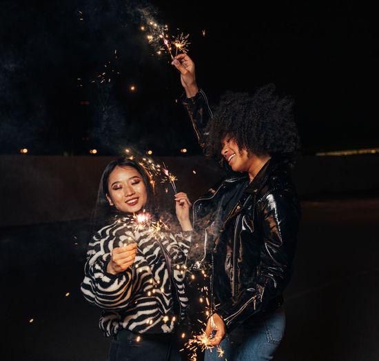 Smiling women holding sparkler standing outdoors