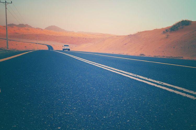 Jeep On Road At Arabian Desert Against Sky