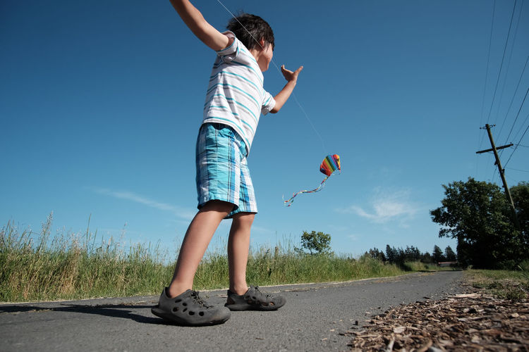 Low Angle View Of Boy Playing With Kite On Road Against Sky