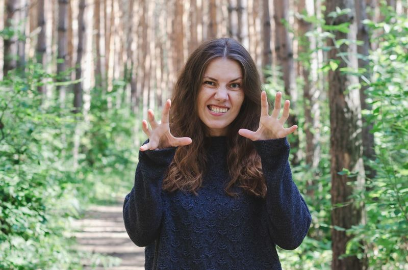 Portrait of woman making face while standing in forest