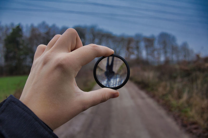 Cropped hand holding lens outdoors