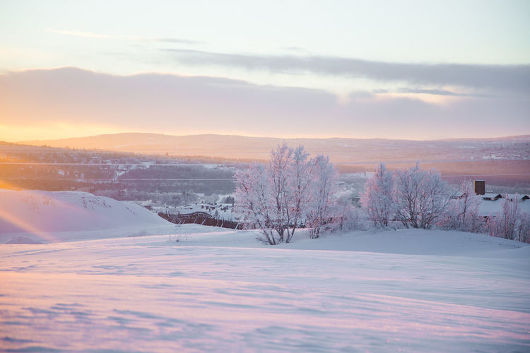 A beautiful evening scenery of a small Norwegian town Roros in winter. Sunset scenery in Norway. Scandinavian town landscape. Nature Winter Landscape Snow Town Sunset Light White Background