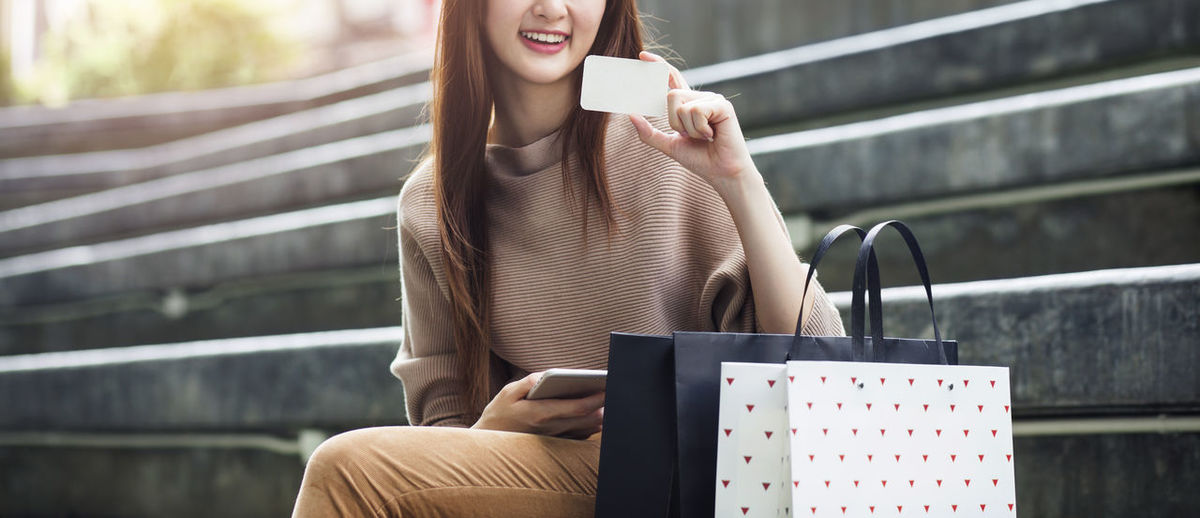 Midsection of smiling young woman holding card while sitting on steps