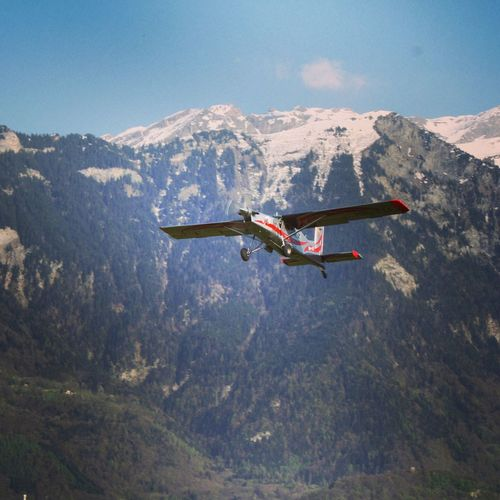 Seaplane flying against mountains
