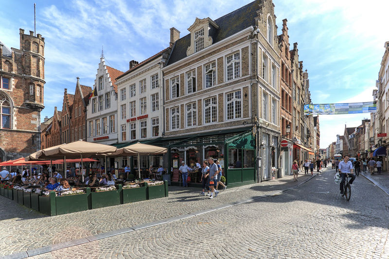 Bruges, Belgium - July 7, 2017: Tourists walking in the market square in the center of Bruges, a beautiful medieval town in Belgium Beer Belgium Brugge Chocolate Dijver Canal Duvel Flanders Panoramic View Provinciaal Hof West Flanders Aerial View Belfry Tower Bikes Bruges Europe Flower French Fries Holland Market Square Medieval Town Mussels