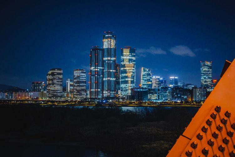 Illuminated buildings in city against blue sky