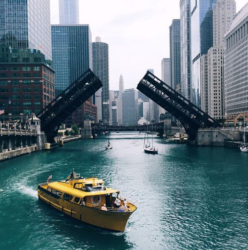 Boats and bridges over chicago river amidst modern buildings