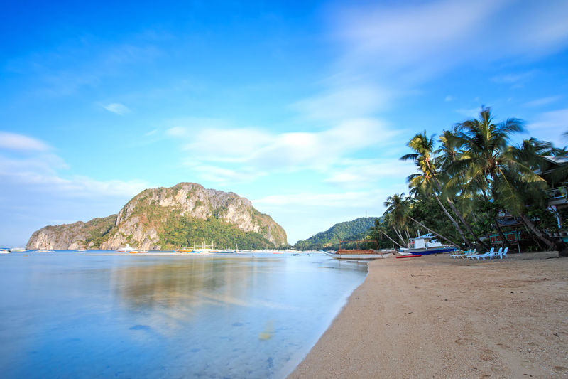 El Nido beach, Palawan in the Philippines ASIA Beach Blue Corong Corong El Nido Mountain Nacpan Palawan Palm Tree Philippines Puerto Princesa Sandy Beach Scenics Sea Sky South East Asia Summer Sunrise Sunset Tranquil Scene Tranquility Tropics Tropics Or Subtropics Underground River Water