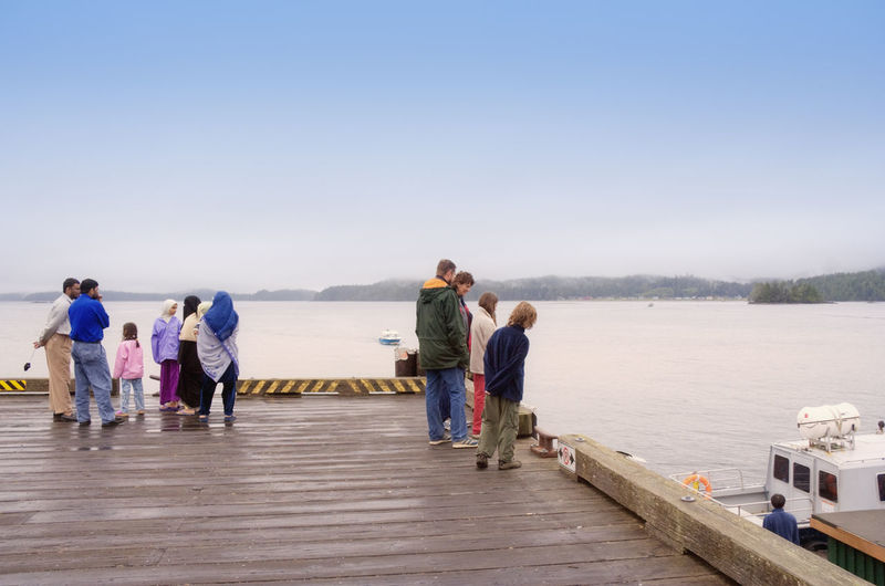 People of different Nationalities on Jetty enjoying view over Pacific Ocean - Diversity in Tofino, Vancouver Island, British Columbia, Canada Burka  Canada Caucasian Clothing Different Diversity Ethnic Family Family Time Family❤ Full Length Headscarf Immigrants Immigration Islam Kids Muslim Nationalism Outdoors Politics Politics And Government Real People Separation Social Issues Togetherness
