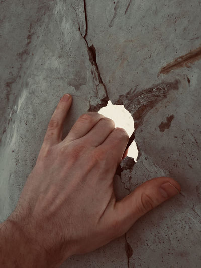 High angle view of person hand on wall