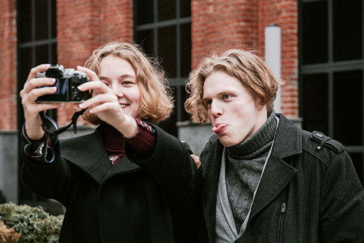 Close-up of friends photographing in city