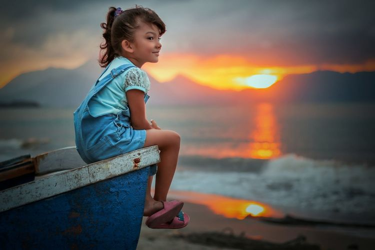 Cute girl sitting on boat at beach against sky during sunset