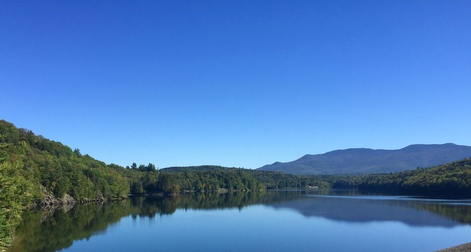 Scenic view of calm lake by mountain against clear blue sky