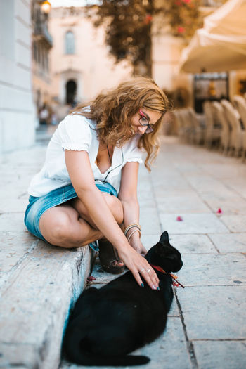 Smiling woman with black cat on footpath in city