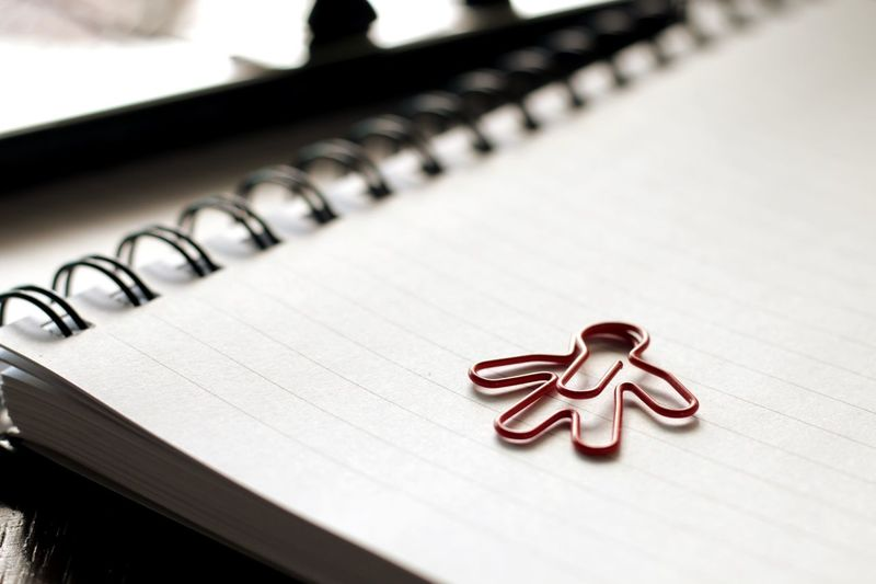 Close-up of human shaped paper clip on spiral notebook
