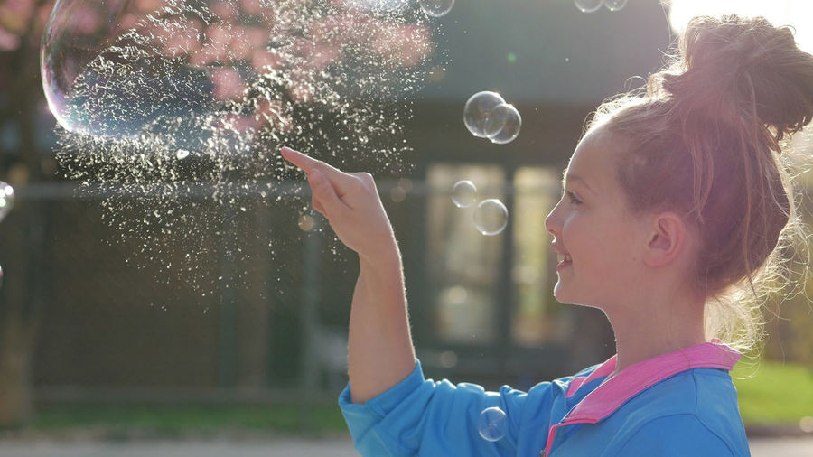 Side view of smiling teenage girl bursting bubble outdoors