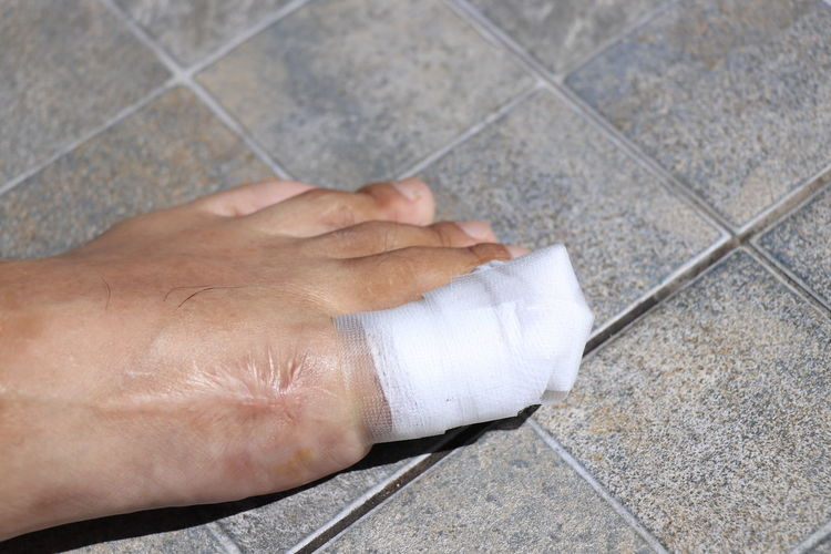 High angle view of person hand on tiled floor