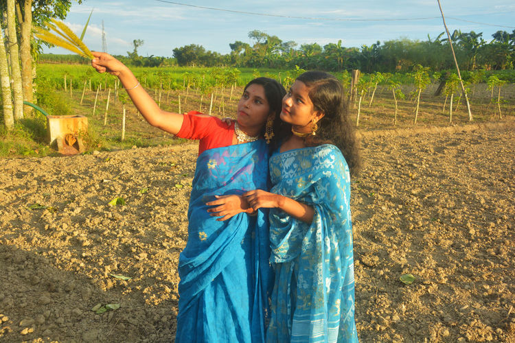 Friends holding crop standing at farm