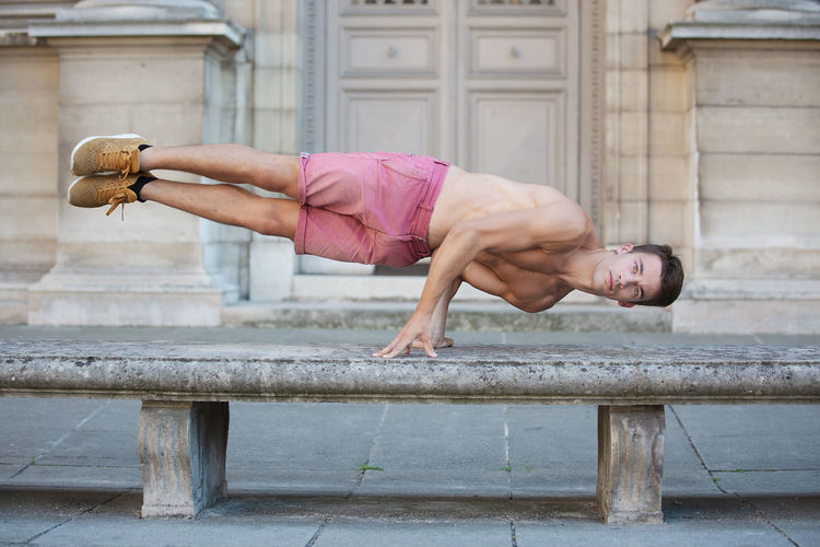 Portrait Of Shirtless Young Man Balancing On Bench Against Building