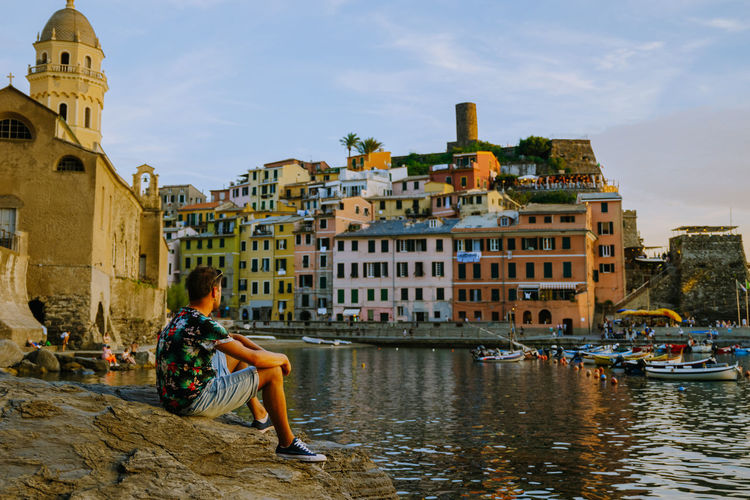 Woman sitting on buildings by canal against sky in city