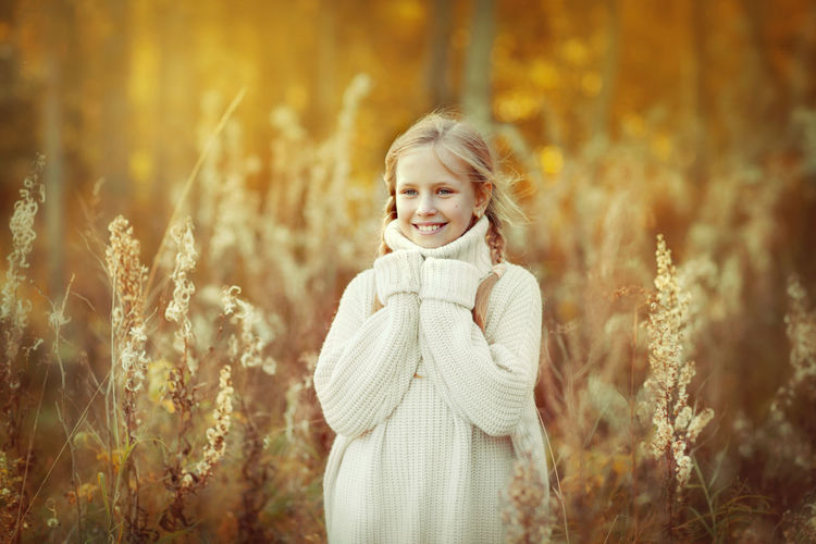 Portrait of a beautiful little girl in a white warm sweater smiling in the autumn forest.