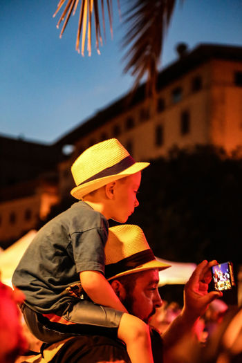 Fatherhood Moments Sitting Architecture Boys Building Exterior Built Structure Childhood City Father Father And Son Focus On Foreground Full Frame Hat Hats High Angle View Leisure Activity Lifestyles Looking Night One Person Outdoors People Real People Sitting On Shoulders Sky