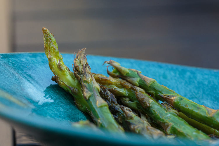 Close up of asparagus in a turquoise bowl