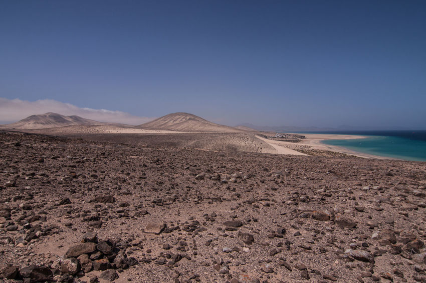 Fuerteventura Arid Climate Beauty In Nature Blue Clear Sky Day Desert Kanarische Inseln Landscape Nature No People Outdoors Sand Sand Dune Scenics Sea Sky Tranquil Scene Tranquility Travel Destinations Water