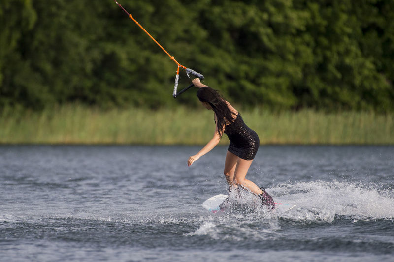 Woman wearing dress while kiteboarding in lake