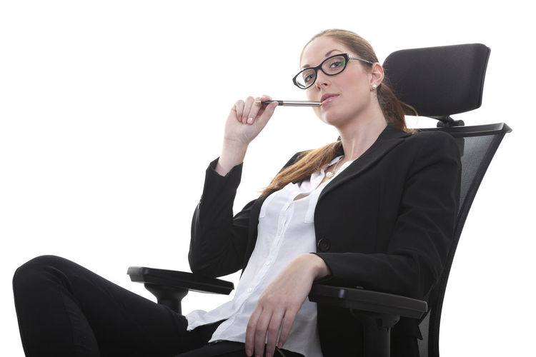 Portrait of businesswoman sitting on chair over white background