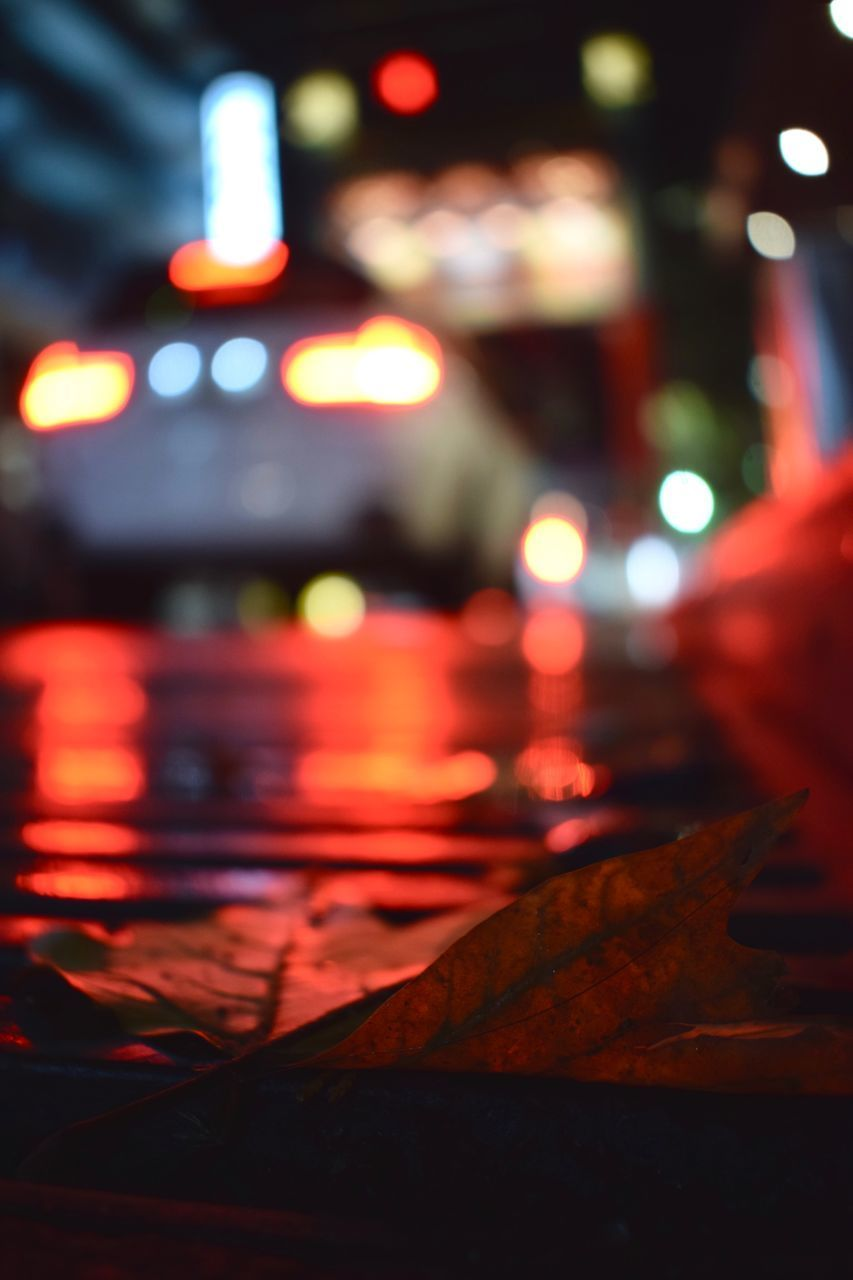 CLOSE-UP OF ILLUMINATED LIGHTS AT CITY STREET