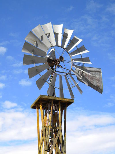 Low angle view of water pump windmill against sky on sunny day