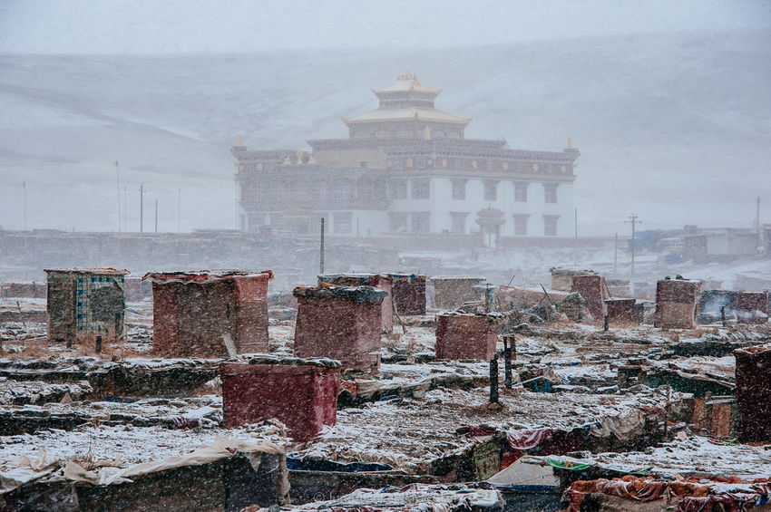 The monastery and the Nuns' Quarter of Yarchen Gar during a blizzard. On the rooftop are study boxes where nuns go in to read Buddhist teachings. 02.03.10. A Journey To Nirvana Blizzard China Culture Documentary Documentary Photography Jun Michael Park Monastery Outdoors Photojournalism Religion Reportage Sichuan Snow Spirituality Storytelling Temple Tibet Travel Travel Photography Winter Yarchen Gar