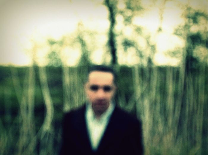 Portrait of young man against blurred trees