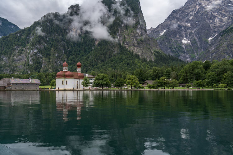 Scenic view of church by lake against mountains