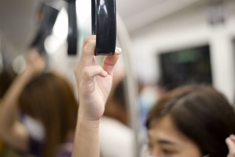 Cropped image of woman holding handle in train